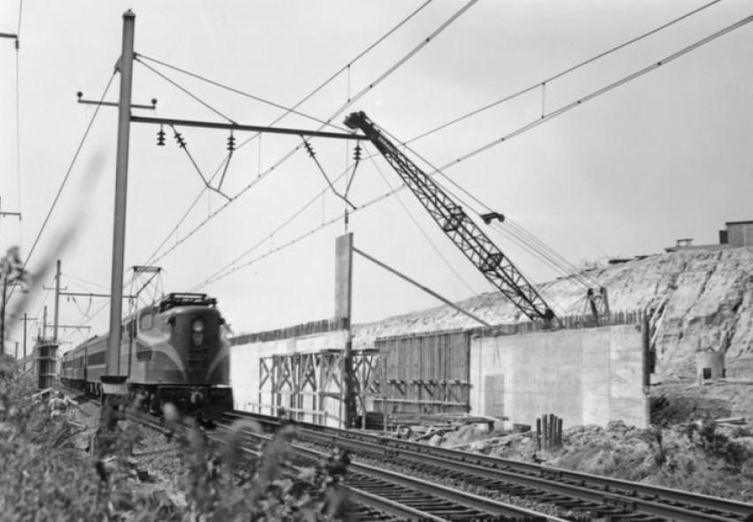 The action at the Pennsylvania RR crossing is shown in this October 1953 photo. An electric commuter train is speeding through the construction site.