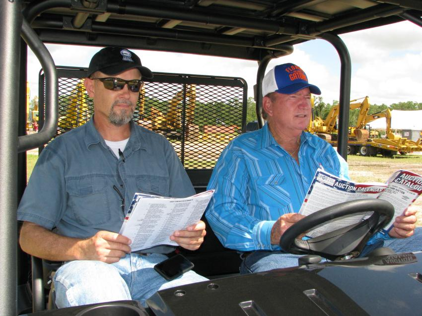 Local contractors monitoring the machine bidding from the comfort of their golf cart are C.J. Bakkes (L) and J.W. Fulwood of Elite Gunite, Plant City, Fla.