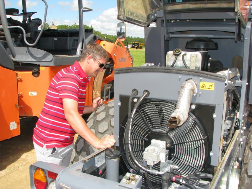 Jason Mashburn of Mashburn Equipment, Ringgold, Ga., inspects the powerplant of a Hamm H7i single drum compactor.