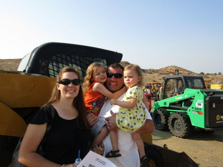 Carrie (L) and husband Derek Wells, holding their future family developers, Luke and Brynn, drove straight through from Salt Lake City to attend this sale. Wells, a developer, is working simultaneously on four projects and needs additional equipment, including this 2008 Caterpillar 262C skid steer.
