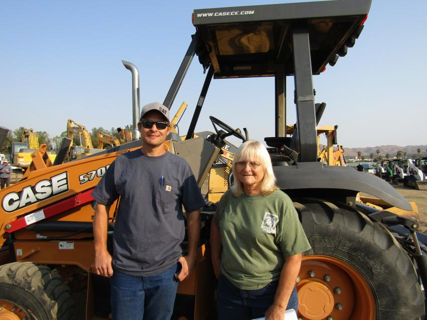 Allan Tillman (L) and his mother, Tanya, of Tillman Construction of Santa Rosa, Calif., lost everything in the recent fires. They came to auction to start to rebuild their equipment inventory. This 2014 Case 570NXT wheel loader is one of several pieces Tanya hopes to leave with.