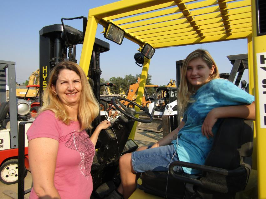Mother and daughter, Carrie (L) and Grace Clifford made it a fun day while searching for additional equipment for their family business, Clifford Electrical in Menifee, Calif. Grace tests out the comfort factor on this 2001 Hyster H35XM industrial forklift.