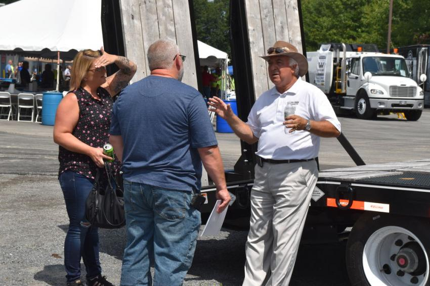 Mike Flynn (R), factory representative of Felling Trailers, brings open house visitors up to date in the latest advancements in hauling technology.