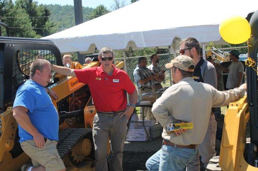 Griff Sansbury (2nd from L), salesman of Carolina Cat, discusses the product line with interested customers.