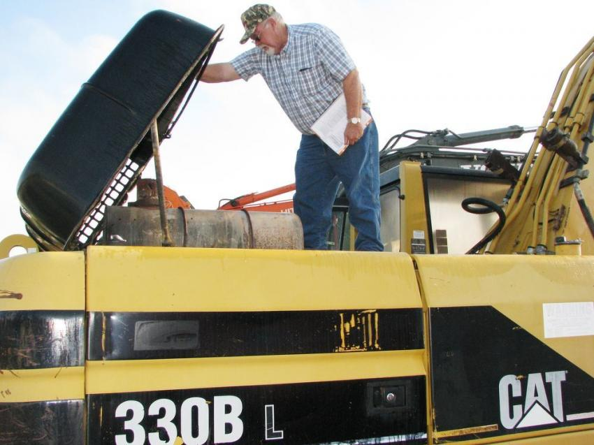 Opening up a Cat 330BL for a complete inspection is Tommy Blair of Blair Block LLC, based in Childersburg, Ala. Blair is looking for a carrier machine for a crusher attachment he bought at a Ritchie sale in Houston.
