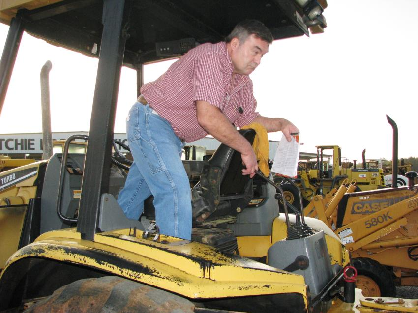 Wendell Cain of Cain & Todd Equipment, Lilburn, Ga., test out a Cat backhoe.
