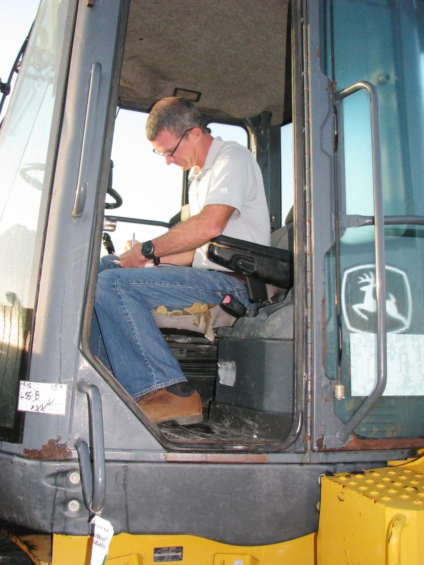 Brett Johnson of Vertical Earth, Cumming, Ga., jots down some notes after test operating a John Deere 624K wheel loader.
