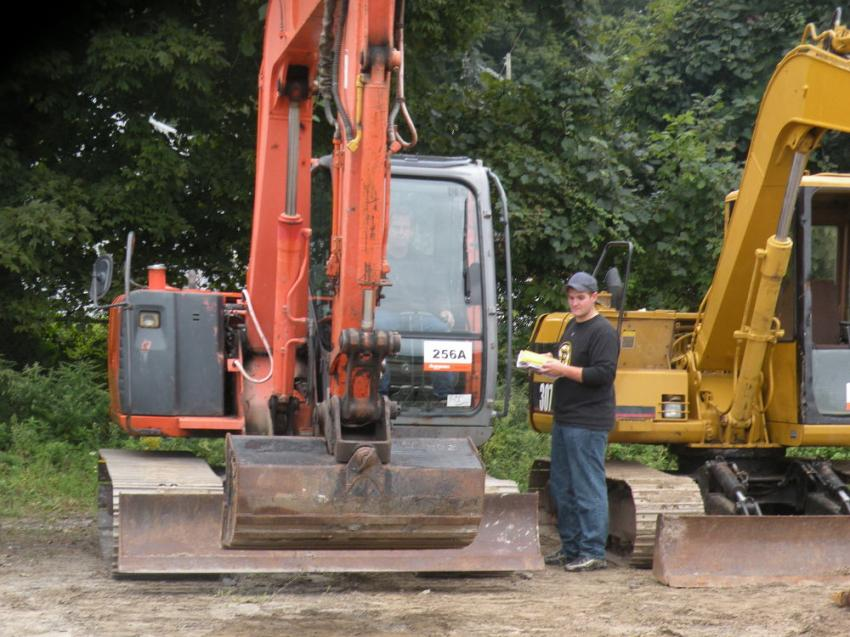 A potential buyer examines the Hitachi ZAXIS 60 excavator.