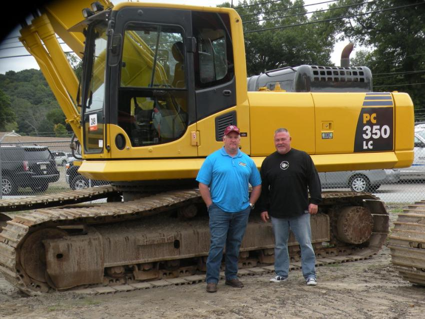 Craig Cypret (L) and Anthony Sacco, who sell and rent heavy equipment at T-Quip in Londonderry, N.H., check out this Komatsu PC350LC excavator.