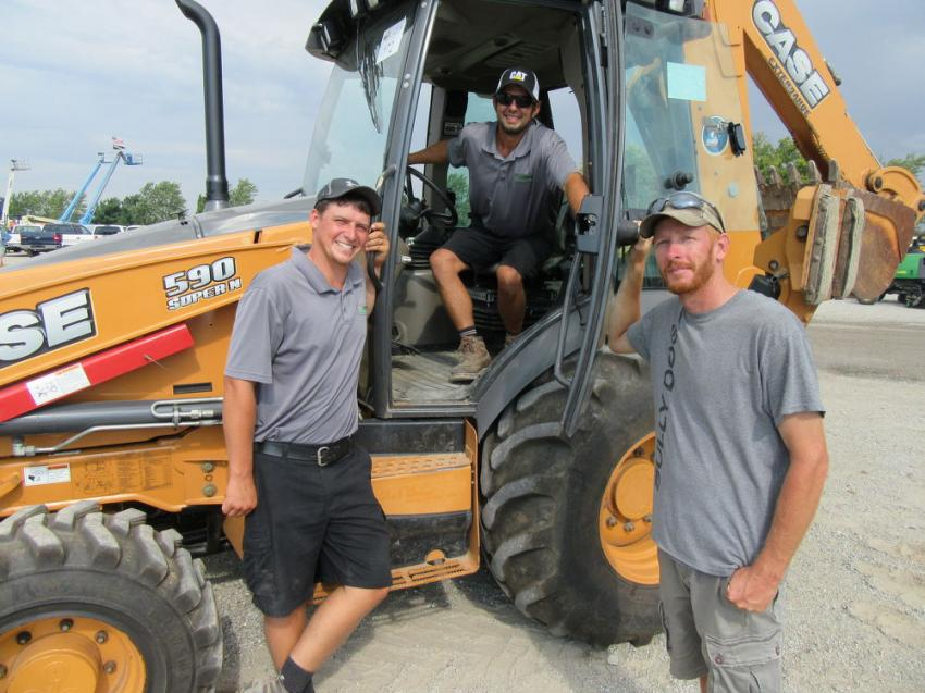 (L-R): Jess White, Garrett Cooper and Jeremy Coffey of Coops Lawn Care gave this Case 590 backhoe the once over at the auction.