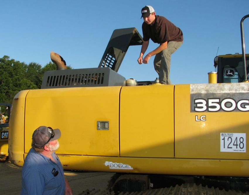 Brian Shelton (L) and Jacob Woodliefo of Shelton Logging & Chipping, Stoneville, N.C., wrap up their inspection of a Deere 350G excavator.
