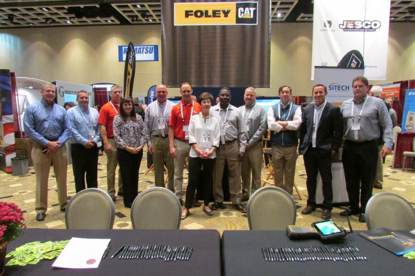 The Foley Cat family, including Ryan Foley, president (second from R), Jamie Foley CEO (third from R) and Susan Connolly, COO (C), poses beneath their banner.
