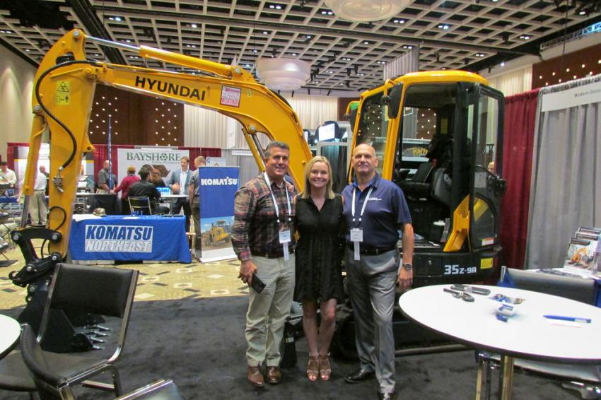 (L-R): At the Modern Group Ltd. booth, Ron D'Ortone, construction sales representative, Brianna Hughes, customer development specialist, and Robert Schumody, municipal sales specialist, pose in front of a Hyundai R35Z-9A compact excavator.