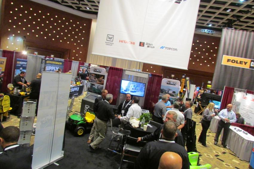 JESCO representatives chat with customers beneath their banner as an equipment video plays in the background.