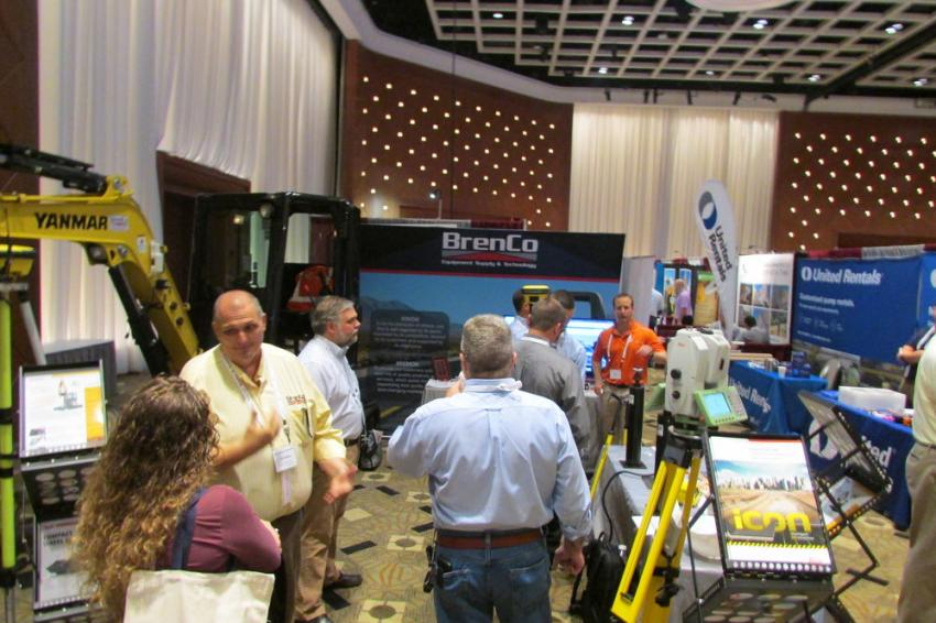 It's a busy day at the BrenCo booth as representatives talk with customers about equipment offerings.