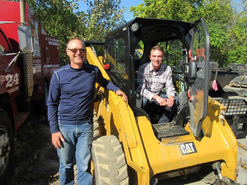 Carl (L) and Andrew of Pallet Services LLC try out a Caterpillar 262D skid steer at the auction.
