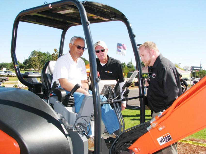 (L-R): Chatur Chhabhaya of CMES, a DOT contractor based in Atlanta, Ga.; Bryan Garner of GeoMax Positioning, Jacksonville, Ark.; and Construction Laser's Stephen Bridges discuss the GeoMax EZDig Touch machine control system on a Kubota KX057-4 mini-excavator.