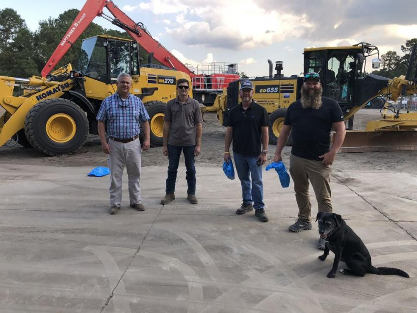 Brian Chappell (L) of Linder Industrial Machinery goes over the Komatsu wheel loaders and motorgraders with Marc Watson, Sanders Brothers in Charleston, S.C.; and Kevin Woodley, Lonny Seleogo and company mascot Figi of Fontaine Construction in Charleston, S.C.