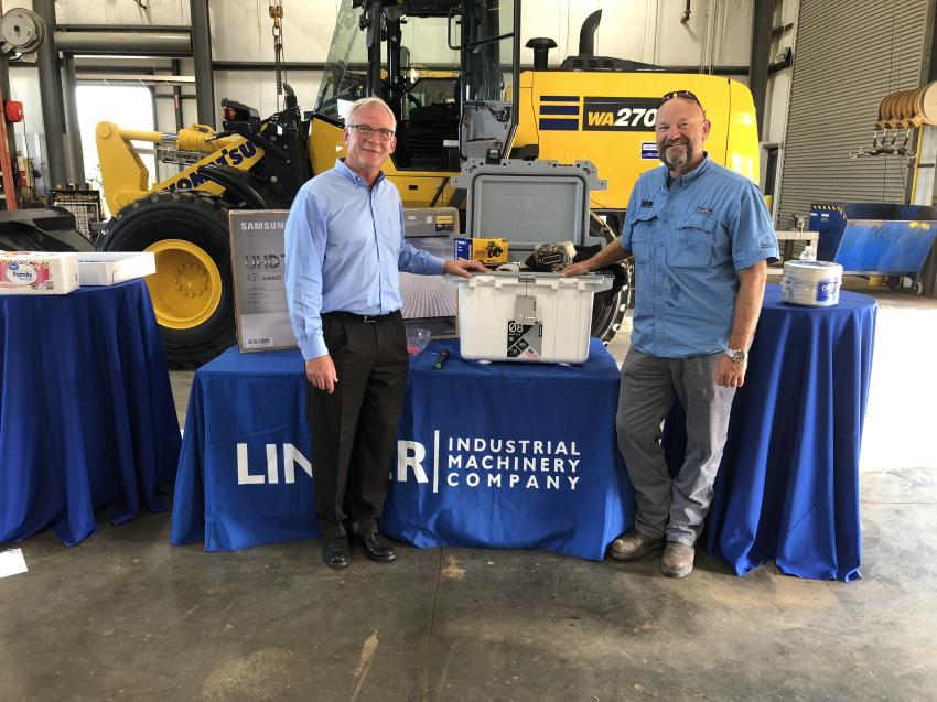 John Coughlin (L), president of Linder Industrial Machinery, presents the door prize to David Young of Vulcan Materials in Greenwood, S.C.