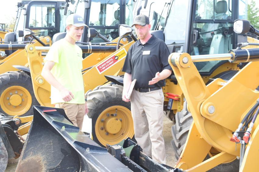 Roger Hanchak (L), owner of Hanchak Landscaping, Sykesville, Md., speaks with Shane Krabal, machine sales representative of Alban CAT, about a few different-sized wheel loaders that he'd like to add to his fleet before winter.
