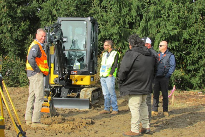 Derrick Ward (L), grade control specialist, discusses machine control with customers.