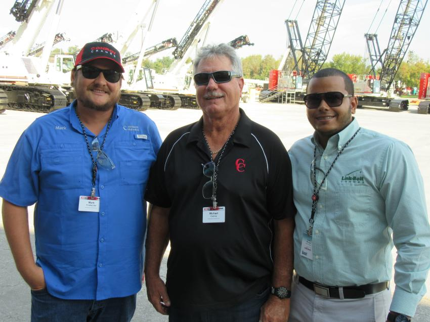 (L-R): Mark Froetschel and Michael Conroy of Prestressed Contractors Inc. join Julio Rivas of Kelly Tractor to review the display of Link-Belt cranes.