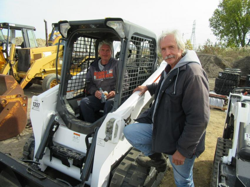 Brothers Tom (L) and Ted Weigienka of Quint Plumbing & Heating discuss a Bobcat T590 compact track loader.