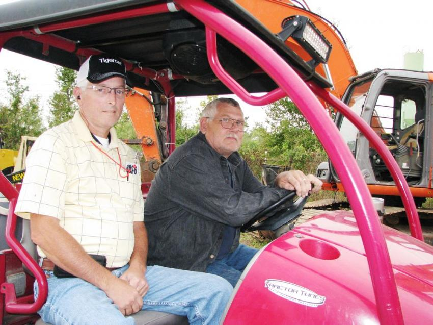 Watching the heavy machine auctioning action from the comfort of their golf cart are Greg Barwick (L) and Jesse Yawn of Barwick Construction & Forestry, Swainsboro, Ga.