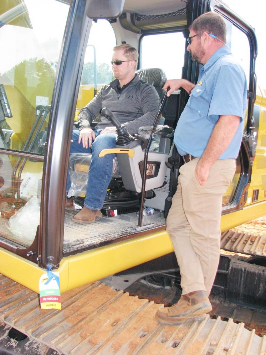 Matt Johnson (in cab) and Jed Knowles, demo operator, both of Yancey Bros. Co., brush up on their operating expertise on the next-generation Cat excavators.