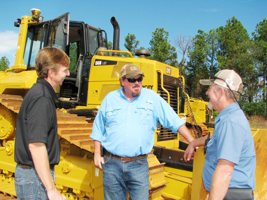 (L-R): Cleve Gambrell, Yancey Bros. Co.; Marc Burrow, Marc Burrow Grading, Covington, Ga.; and Matt Johnson, Yancey demo operator, talk about Burrow's latest purchase, a D6N dozer with Grade Control that is just like one of the machines being demoed.