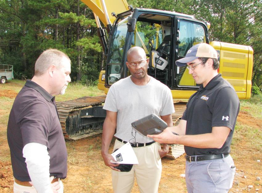 (L-R): Lance Pitts, Yancey Bros.; Khayyan Dixon of K. Dixon Construction Company, Conyers, Ga.; and Tyler Phelps of Sitech South go over some 3-D site data on a handheld unit showing the relationship between the data collectors and the machines.