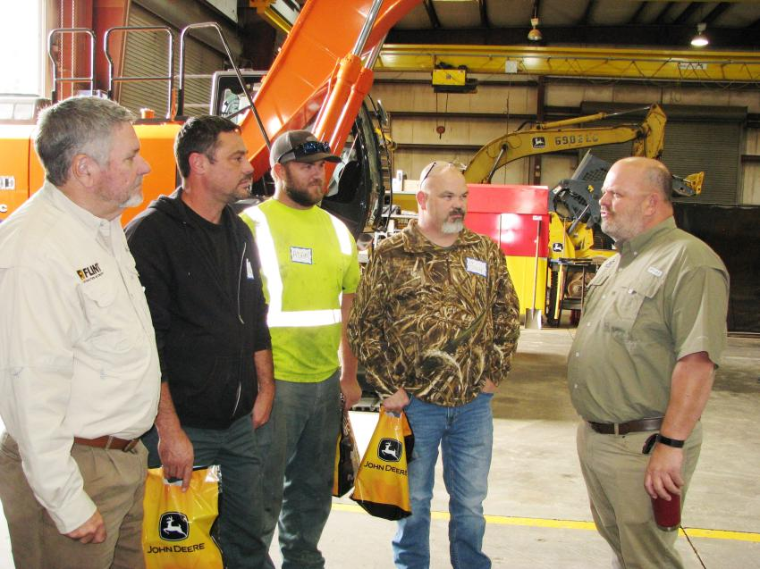 (L-R): Bob Simmons of Flint Construction & Forestry Division; Donnie LaCroix, Adam Findlay and Guy Stillinger of Banks Construction, Charleston, S.C.; and Tim Houchens, also of Flint, discuss the local construction industry.