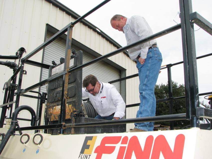 Dean Sippel (L), FINN Corporation regional sales manager, and Tony Wilson of L-J Inc., Columbia, S.C., inspect the agitators on a FINN T120 hydroseeder on display.