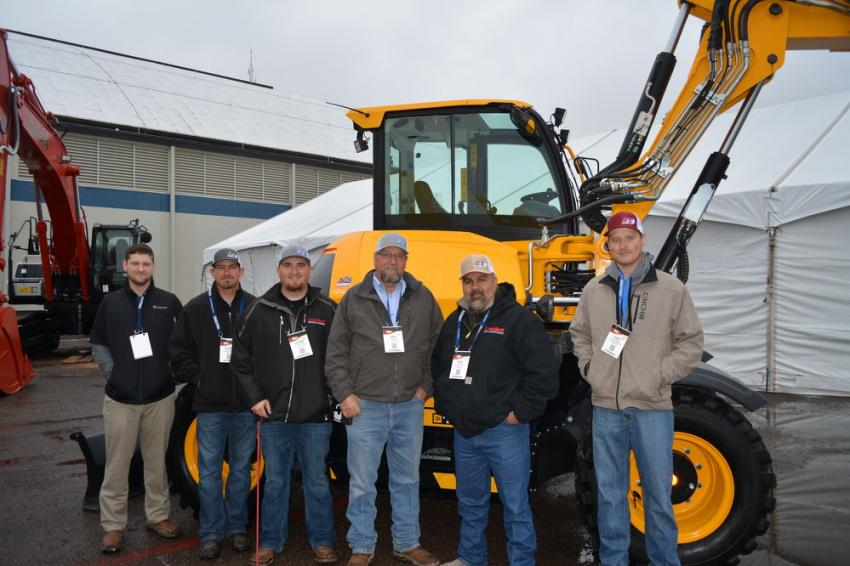 (L-R): Stuart Fox, Blaine Maturin, Jeremy Foster, Kirk Daniel, Kent Rivas and Jared Wilhoit, all of Cisco Equipment's Odessa branch, endured the cold, wet weather to answer customers' questions. Shown is JCB's Hydradig 110W.