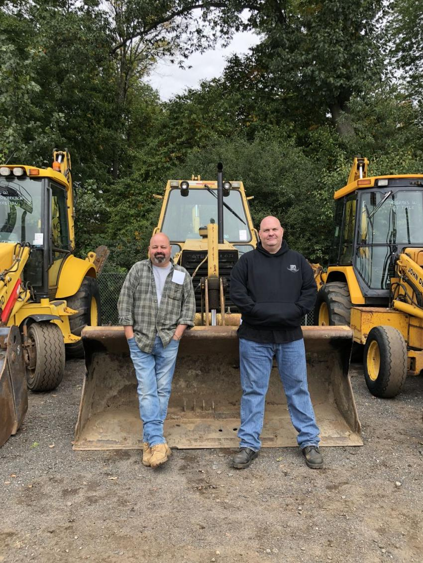 Chris Lavelle (L) and Dave Isakson, both of South Hadley, Mass., check out the tractor loader backhoes.
