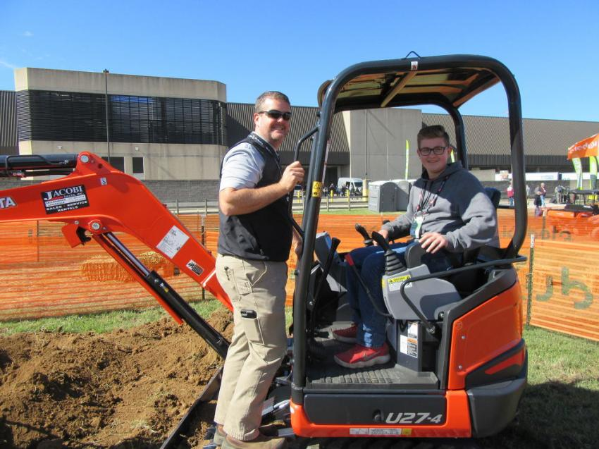 Kubota Tractor Corporation's Matt Guentter (L) gives some operating tips to young entrepreneur, Karson Fosdick of Karson's Lawn Care, Brazil, Ind.