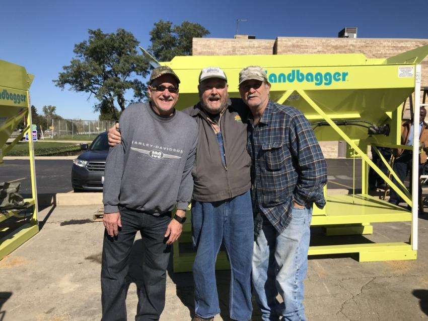Charlie Anderson (C), Andy's Landscaping, gives The Sandbagger's Tim Vandergrift (L) and longtime pal Roger Hoegarden, Hoegarden Excavating, a jovial embrace for the camera after seeing what The Sandbagger machine can do for contractors..