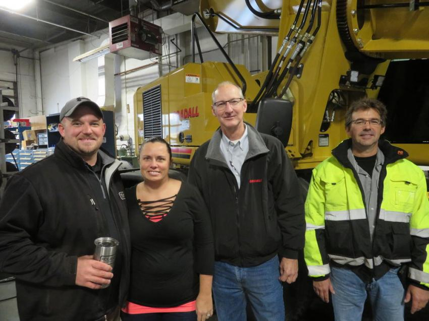 (L-R): Kyle McDowell, Roland Machinery Co.; his wife, Jennifer; Gary Cain, Gradall Industries Inc.; and Steve Oltmanns, Roland Machinery Co., gather in front of the Gradall XL4100.