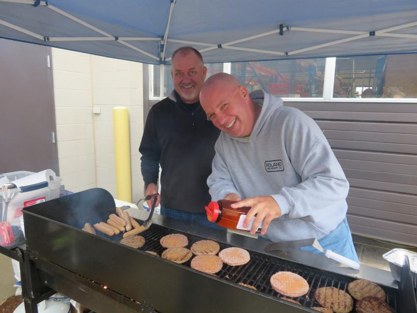 Taking care of the cooking duties are Jay Germann (L), general manager and used equipment manager of Roland Machinery Co.; and Paul Walters, sales and rental coordinator.