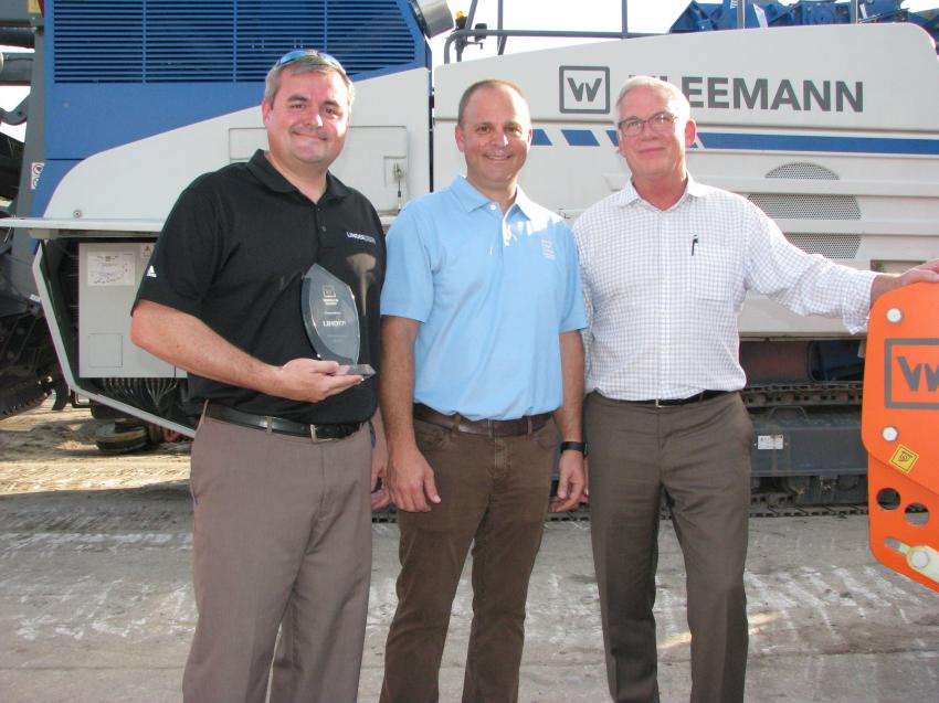 Corey Wall (C), Wirtgen Group district sales manager, presented Chris Wilkes (L) executive vice-president and John Coughlin, president of Linder Industrial Machinery, with a plaque commemorating Linder's 65th anniversary at the company's Plant City open house.