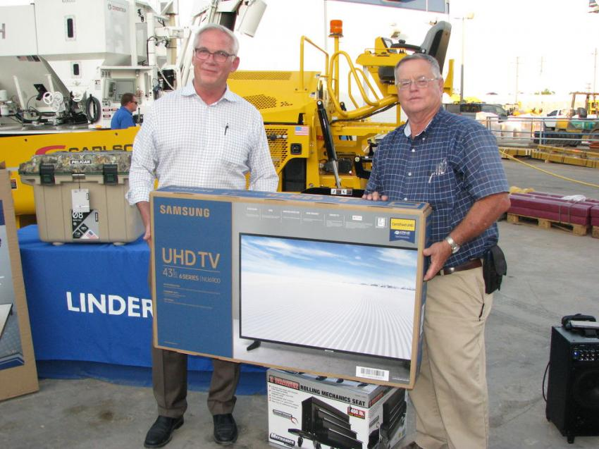 Winner of the flat-screen TV at the Plant City open house is David Bottom (R) of Clark Hunt Construction, Clearwater. Presenting the prize is Linder's president, John Coughlin.