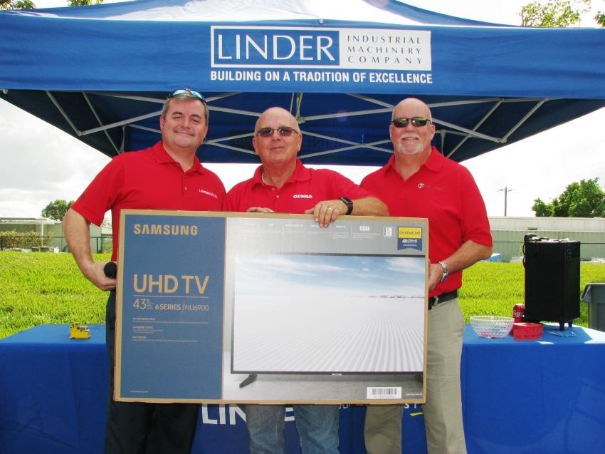 The big winner at the Miami open house was Don Kremke (C) of Ozinga, based in Davie, Fla. He was presented with the grand prize of a flat-screen TV by Linder's Chris Wilkes (L) and Allen Perko of Paladin, which donated the grand prize for the event.