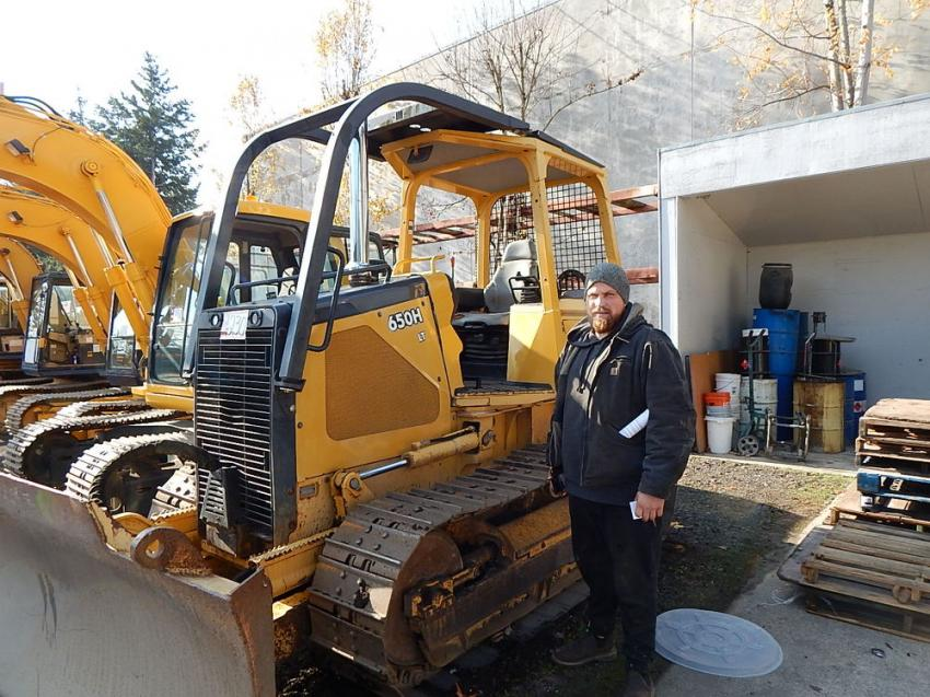 "Checking out this nice John Deere 650H LT dozer is Nikita Sloboda, NNS Construction, Edgewood, Wash. ""Good weather and some great equipment make for a great auction,"" said Sloboda."