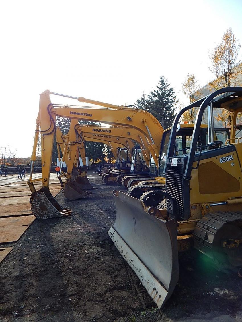 This John Deere 650H crawler dozer sits ready for auction alongside a variety of Komatsu excavators.