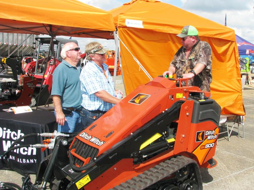 Talking about the features of a Ditch Witch SK800 mini-skid steer are (L-R) Ronnie Burch and Gary Morris of Ditch Witch of Georgia, Albany, Ga.; and Buddy Weigelt of Buddy's Tractor Service, Crystal River, Fla.