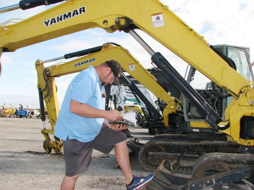 John Bollinger of Pioneer Equipment, Savannah, Ga., looks over his notes and contemplates his bidding strategy on a pair of Yanmar SV100 excavators.