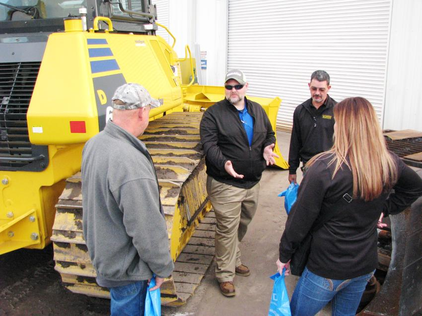 Sharing some information with his Jacksonville guests on the Komatsu D61PXi dozer and the Intelligent Machine Control technology built into the machine is Linder Industrial Machinery's Mike Teston (C).