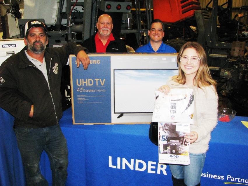 Big prize winners at the Jacksonville event included Phillip Feora (L) of United Brothers Development, who won a Samsung flat screen TV and Montana Morris (R), the daughter of a staffer at Hrustic Brothers Trucking, Jacksonville, Fla., who won four tickets for the mid-December Jacksonville Jaguars vs. Washington Redskins game. At back are Allen Perko (L) of Paladin, the manufacturer that donated the TV, and Jim Nucci, Linder North Florida regional manager.