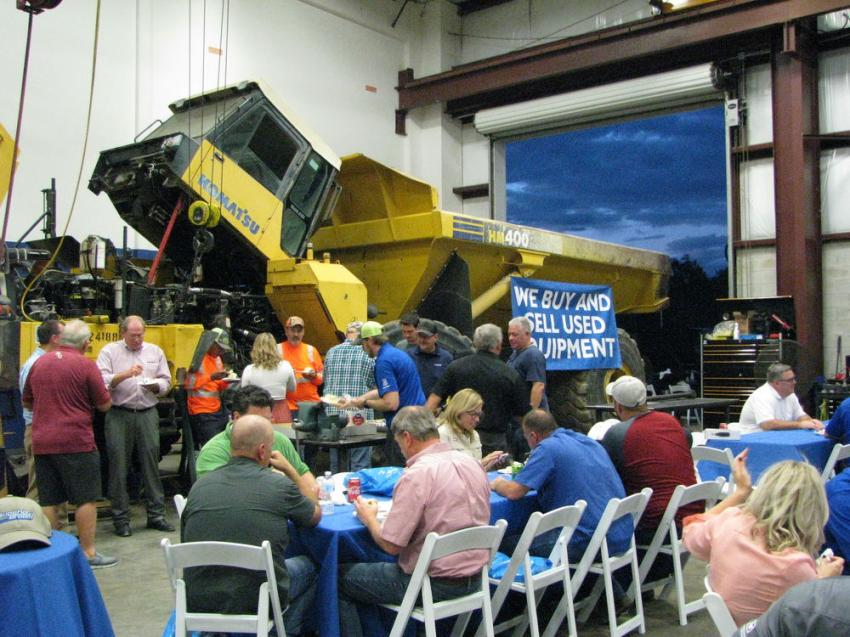 As darkness set in during the Orlando open house, the crowd gathered in the shop area around the Komatsu articulated truck rebuild for some 65th anniversary cake.