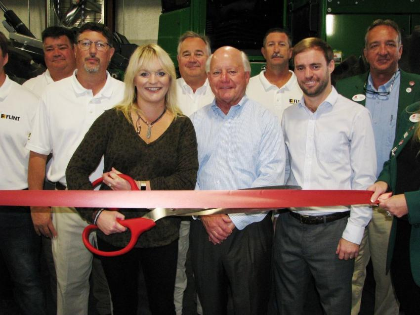 Flanked by Flint staffers and the local Chamber of Commerce, Christie, Chris and Flin Cannon, owners of Flint Construction & Forestry, prepare to cut the ribbon for their new Valdosta branch location.